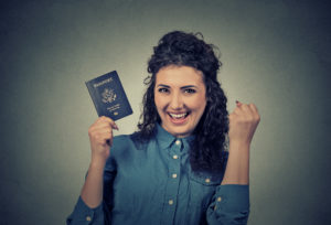 Portrait attractive young excited woman with USA passport isolated on gray wall background. Positive human emotions face expression. Immigration travel concept